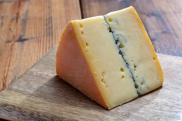French semi-soft cow milk cheese morbier from Franche-Comte region with thin black layer and strong aroma