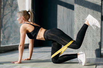 Fitness woman uses elastic band for sport Fotomurales