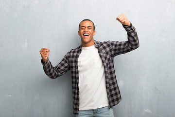 Young african american man with checkered shirt celebrating a victory in winner position