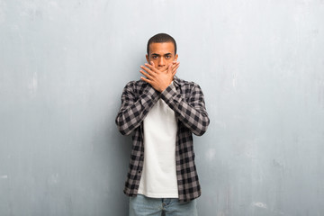 Young african american man with checkered shirt covering mouth with hands for saying something inappropriate