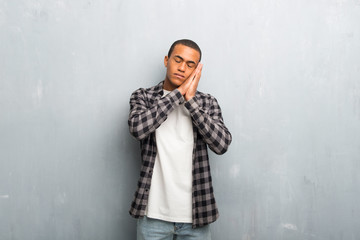 Young african american man with checkered shirt making sleep gesture in dorable expression