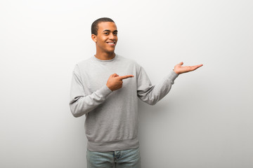 African american man on white wall background holding copyspace imaginary on the palm to insert an ad