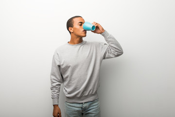 African american man on white wall background drinking hot coffee