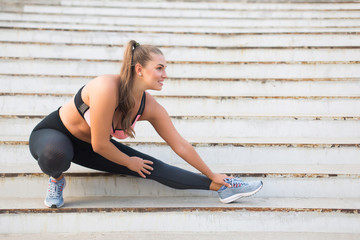 Joyful plus size girl in sporty top and leggings happily stretching on stairs while spending time outdoor