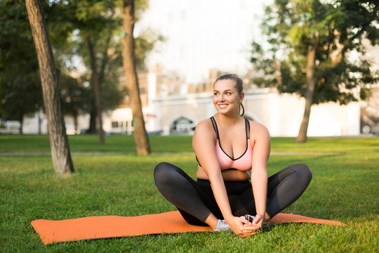 Young beautiful smiling plus size woman in pink sporty top and leggings sitting on orange yoga mat happily looking aside while spending time in park