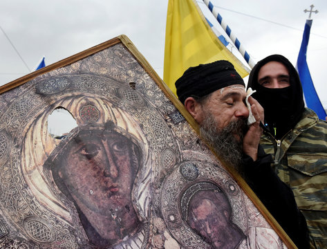 A priest reacts as he holds a cracked icon depicting the Virgin Mary holding the Christ child during a demonstration against the agreement reached by Greece and Macedonia to resolve a dispute over the former Yugoslav republic's name, in Athens