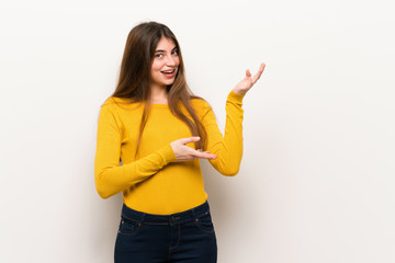 Young woman with yellow sweater extending hands to the side for inviting to come