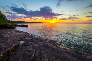 Scenic Summer Sunset. Sunset over the horizon of Lake Superior on a wild remote rocky coastline in Copper Harbor, Michigan.