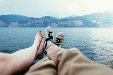 Boy and girl are enjoying their holiday evening: Sneakers and barefoot feet, lake and mountains