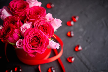 Pink roses bouquet packed in red box and placed on black stone background with copy space. Valentines day or Romantic concept.