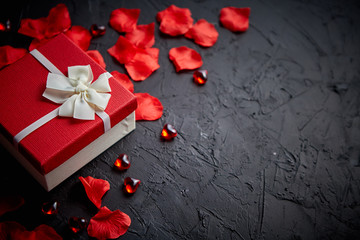 Gift box on black stone table. Sweet romantic holiday background with rose petals, acrylic heart shaped decoration. Valentines day background. Top view with copy space.