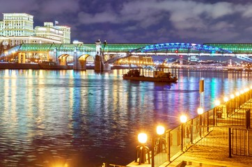 Night vibrant view of illuminated Moscow river and embarkment with boat, bridge and colorful water reflectons