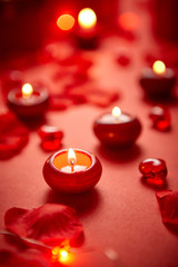 Romantic dinner decoration. Red candles, flower petals, on the table. Selective focus shot. Valentine or Love concept.