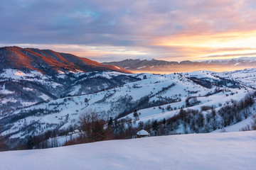winter sunrise in mountains. beautiful carpathian countryside. the sky is on fire. rural area with rolling hills. good morning wonderful world