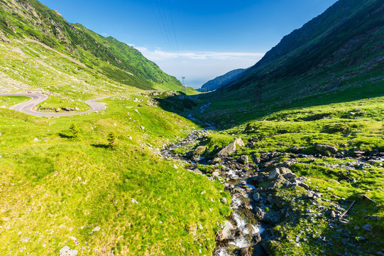 balea stream of fagaras mountains. wonderful serpentine of transfagarasan road on the left side. beautiful summer scenery. power lines along the valley. discover romania
