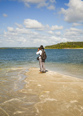 Tourist taking pictures at the tip of Coroa do Aviao islet, Itamaraca island on the right - Pernambuco, Brazil