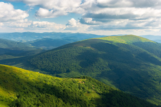 beautiful landscape of carpathian mountains. grassy alpine meadows, deep valleys. wonderful sunny weather at sunset in summer. fluffy clouds on the blue sky