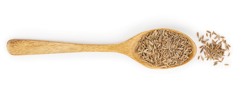 Cumin or caraway seeds in wooden spoon isolated on white background. Top view