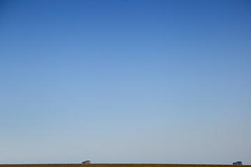 A minimalist image of Iceland in which two cars are seen far away under a big blue sky without clouds