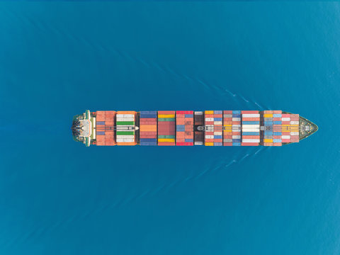Aerial top view container ship at sea port and working crane bridge for loading container, logistic business, import export, shipping or transportation.