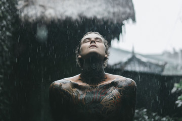 tattooed man posing in the rain