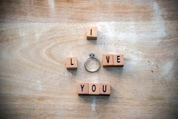Heiratsantrag mit Diamantring aus Holzwürfeln  auf Holzuntergrund