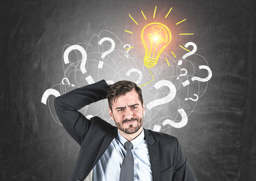 Confused businessman, question marks and idea