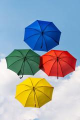 4 fliegende Regenschirme in den Farben rot grün blau und gelb