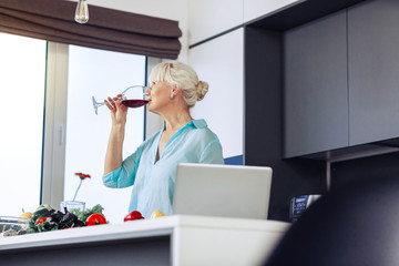Delighted nice woman drinking wine at home