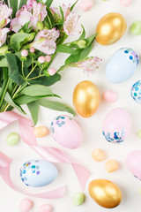 Festive Easter background with decorated eggs, flowers, candy and ribbons in pastel colors on white. Copy space