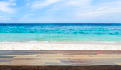 Empty table top for product display montage. Tropical paradise beach and ocean blurred in the background.
