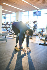 Disabled man with amputee leg exercising in fitness club
