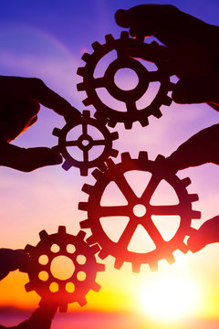 gears in the hands of people on the background of the evening sky, sunset. interaction, teamwork.