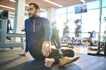 Bearded athlete with amputee leg sitting on the floor and resting in health club