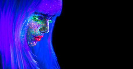 Fashion model woman in neon light. Beautiful model girl with colorful bright fluorescent makeup isolated on black. Ultraviolet, UV