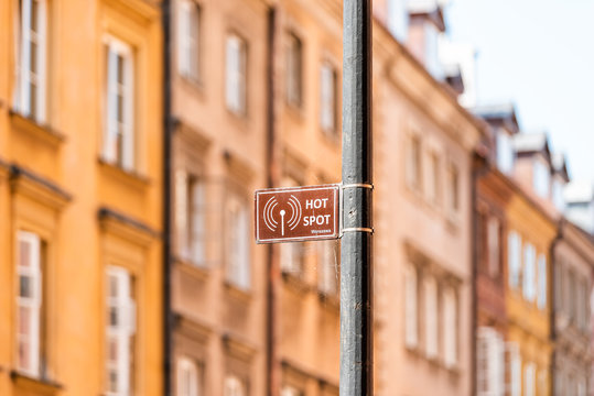 Warsaw, Poland Famous old town capital city architecture during sunny summer day cityscape background and closeup of sign for Warszawa Wifi Hot Spot on pole