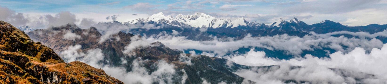 Panorama der atemberaubenden Aussicht auf schneebedeckte Gipfel der Anden in einem Wolkenmeer von einem Pass in über 4000 Meter Höhe während der Wanderung auf dem Inka Trail in Peru