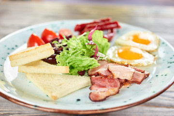 Sliced white bread, ham and lettuce salad closeup. White plate with food.