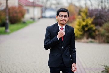 Indian young man at glasses, wear on black suit with red tie posed outdoor.