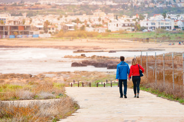 Adult man and woman stroll along the promenade in the afternoon