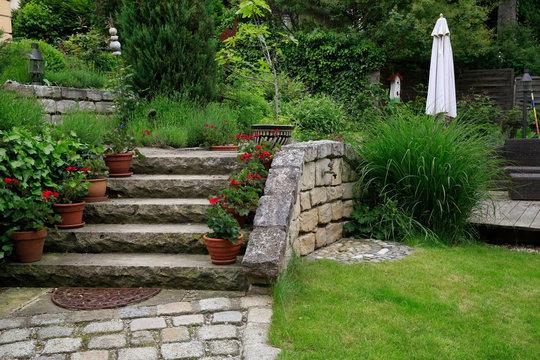 Terrassenförmige Gartengestaltung eines Hanggrundstücks: Treppe und Mauer aus Natursteinen und Holzterrasse mit Gartenmöbel