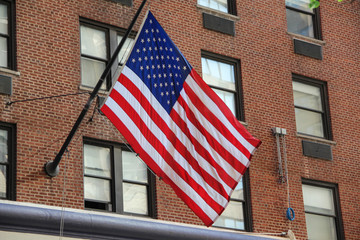 The flag of the United States or the star spangled banner waving on the rooftop of a fire brigade in New York city