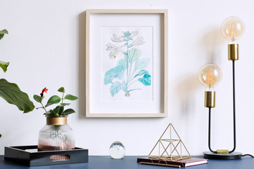 Home interior floral poster mock up with vertical wooden frame, table lamp, plants, accessories  on the grey wall background. Concept with navy blue shelf.