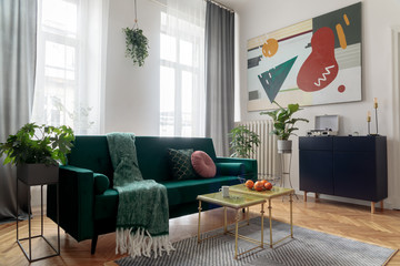 Sunny and bright luxury home interior with design velvet sofa, armchair, tables, pouf, commode and accessroies. White walls with painting. Sunny view. Stylish decor of sitting room. Big windows.