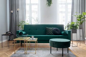 Bright and sunny luxury home interior with design green velvet sofa, furniture, armchair, gold coffee tables, pouf and accessroies.  Big windows. A lot of plants. Stylish decor of living room.