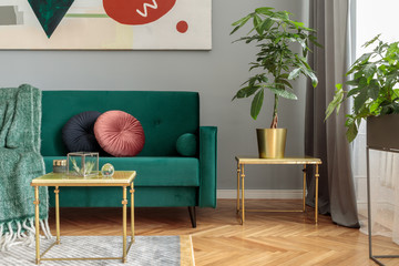 Luxury and modern home interior with green velvet design sofa, coffee tables , color pillows, blanket Tropical plants in metal stand. Grey walls with abstract painting. Stylish decor of living room.