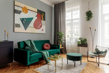 Luxury and stylish  interior with green velvet design sofa, armchair, tables and pouf. Tropical plants in design stand. Grey walls with abstract painting. Stylish decor of sitting room. Big windows.