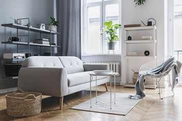 Modern and bright nordic living room with design sofa, coffee table, plants, stylish accessories and bookstand on the grey wall. Brown wooden parquet. Concept of minimalistic interior.