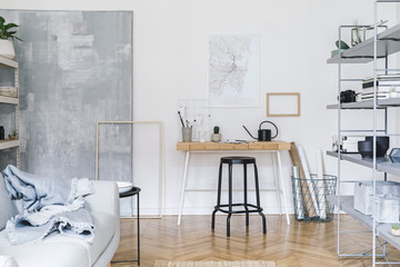 Stylish nordic home interior with wooden desk, grey and white bookstand with accessories, design grey sofa and  modern furniture. Open space and living room for artist, freelancer. Mockup poster frame
