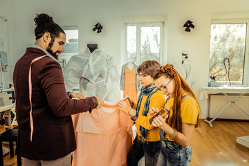 Son helping his father holding light pink fabric while designing clothes